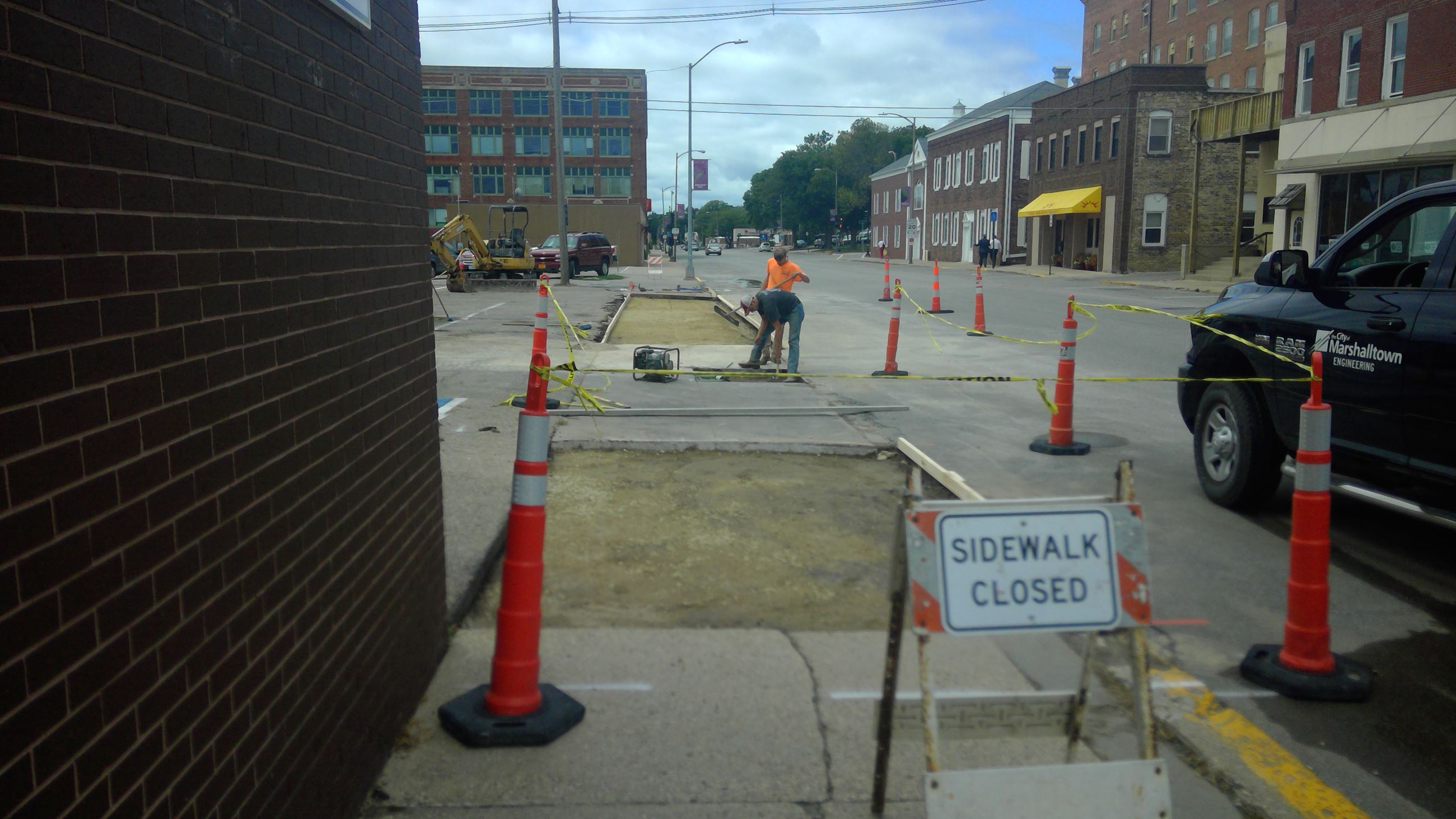 Construction workers working to replace pieces of sidewalk.