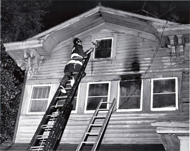 Firefighter at Top of Ladder Using Axe on House Window