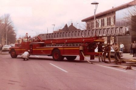 Old Fire Truck With Fighters Pulling Out Hose